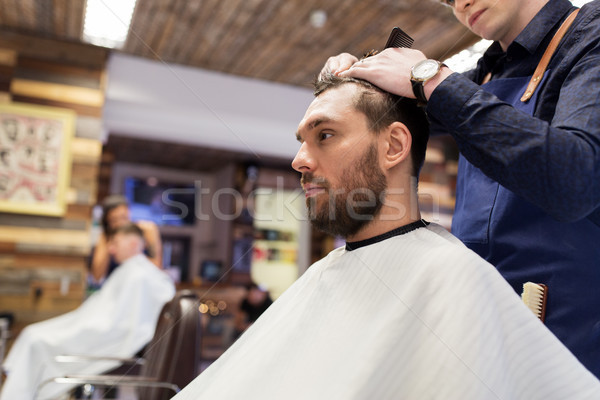 man and barber cutting hair at barbershop Stock photo © dolgachov