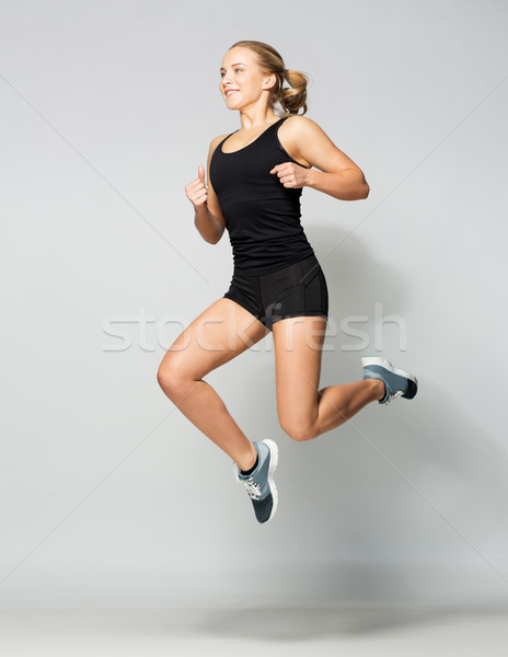 young woman in black sportswear jumping Stock photo © dolgachov