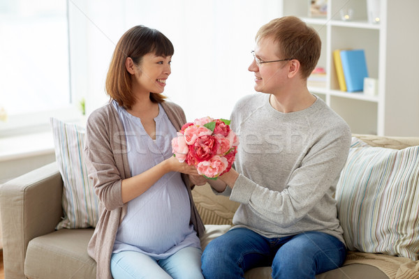 happy husband giving flowers to his pregnant wife Stock photo © dolgachov