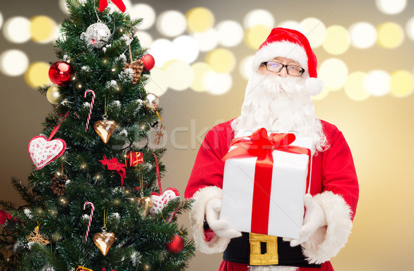 santa claus with gift box at christmas tree Stock photo © dolgachov
