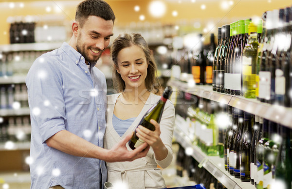 couple with wine and shopping cart at liquor store Stock photo © dolgachov