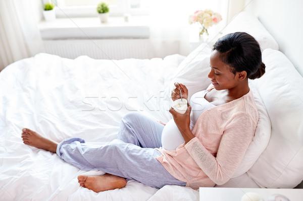 Mujer embarazada comer yogurt cama embarazo personas Foto stock © dolgachov