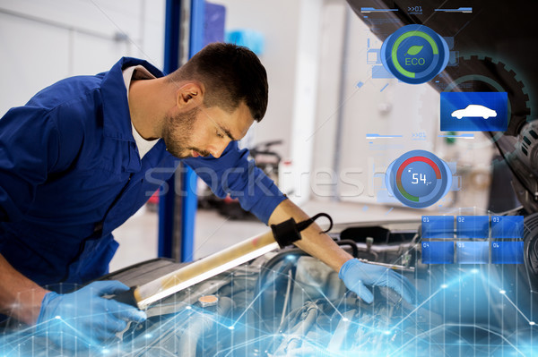 mechanic man with lamp repairing car at workshop Stock photo © dolgachov