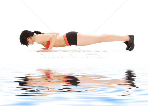 woman practicing four-limbed staff pose Stock photo © dolgachov