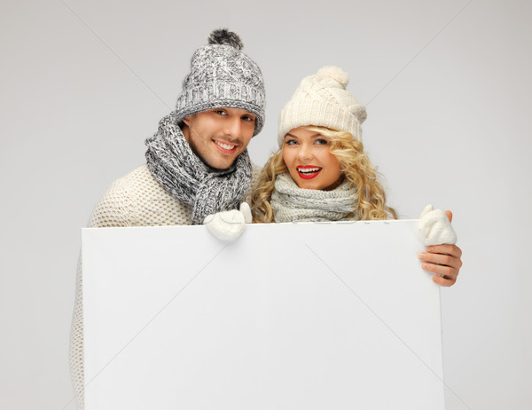 couple in a winter clothes holding blank board Stock photo © dolgachov