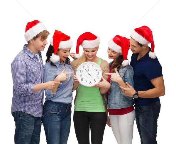 Groep glimlachend studenten klok tonen 12 Stockfoto © dolgachov