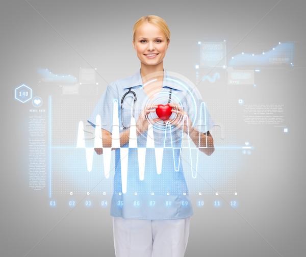 smiling female doctor or nurse with heart Stock photo © dolgachov
