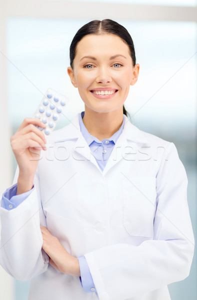 smiling young doctor in cabinet with pills Stock photo © dolgachov
