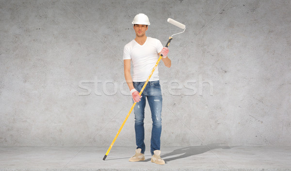handsome painter in helmet with paint roller Stock photo © dolgachov