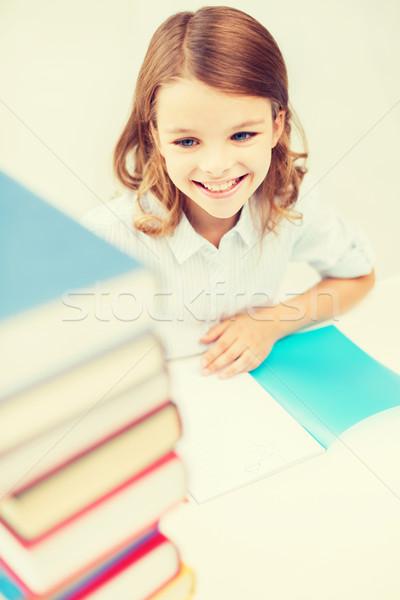 smiling little student girl with many books Stock photo © dolgachov