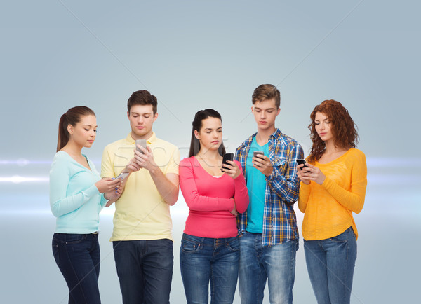 group of serious teenagers with smartphones Stock photo © dolgachov
