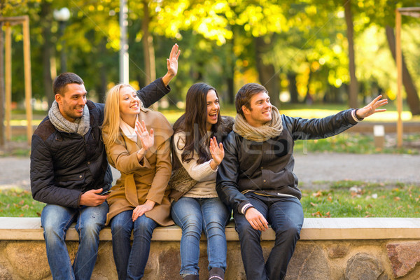 group of smiling friends waving hands in city park Stock photo © dolgachov