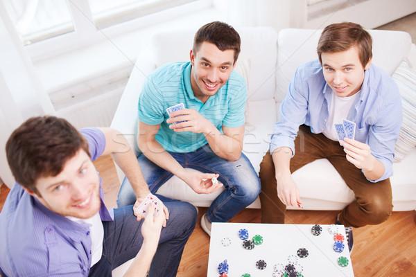Drie glimlachend mannelijke vrienden speelkaarten home Stockfoto © dolgachov