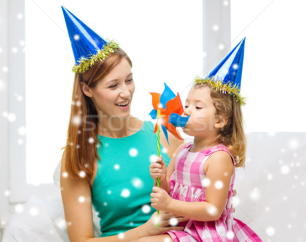 mother and daughter in party hats with pinwheel Stock photo © dolgachov