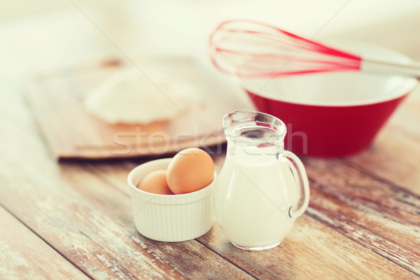 jugful of milk, eggs in a bowl and flour Stock photo © dolgachov