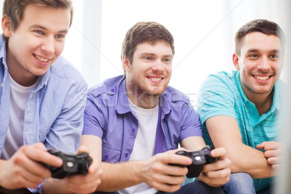 Glimlachend vrienden spelen video games home vriendschap Stockfoto © dolgachov