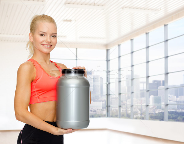 smiling spory woman holding protein jar Stock photo © dolgachov