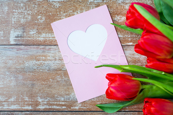 Stock photo: close up of tulips and greeting card with heart