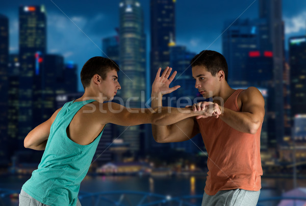 young men fighting hand-to-hand Stock photo © dolgachov