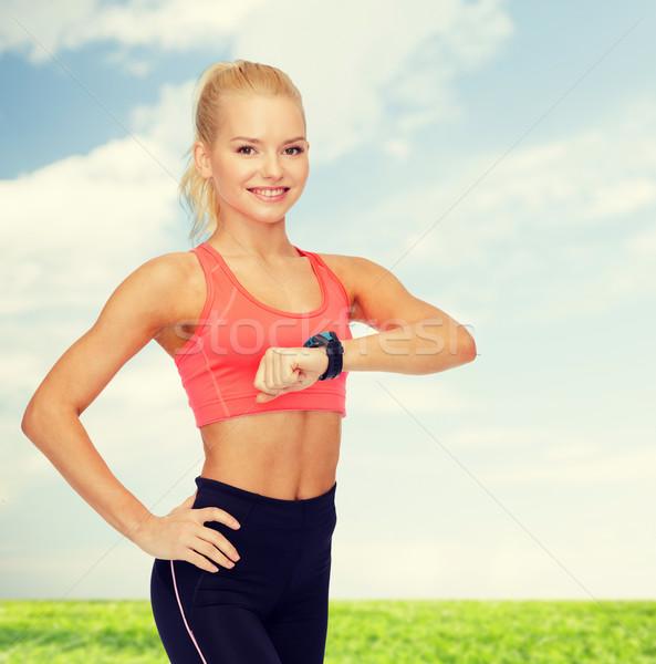 Glimlachende vrouw hartslag monitor hand fitness technologie Stockfoto © dolgachov