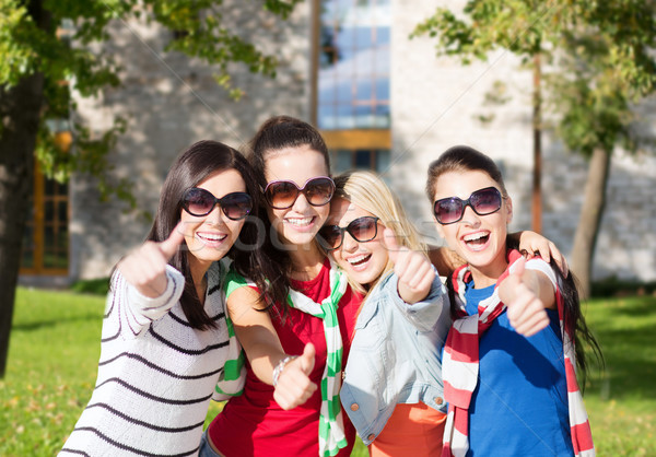 happy teenage girls showing thumbs up at campus Stock photo © dolgachov