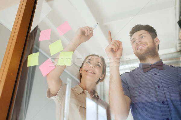 happy creative team writing on blank office glass Stock photo © dolgachov