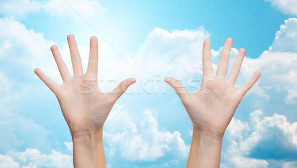 two woman hands making high five over blue sky Stock photo © dolgachov