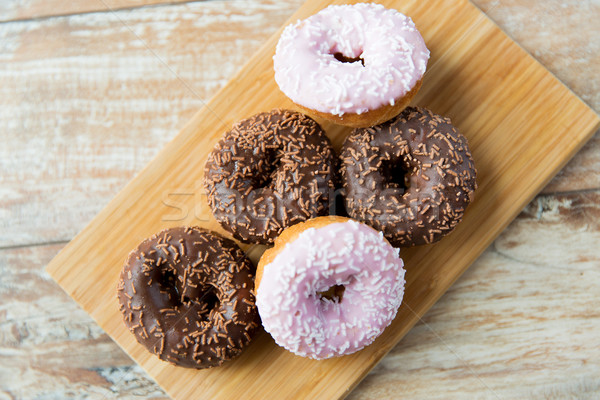Stock photo: close up of glazed donuts pile on table