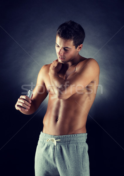young male bodybuilder applying pain relief gel Stock photo © dolgachov