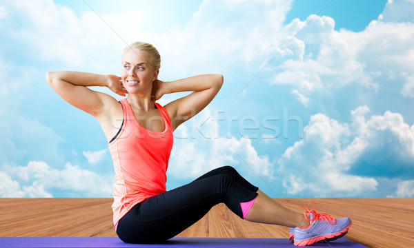 smiling woman doing sit-up on mat over clouds Stock photo © dolgachov