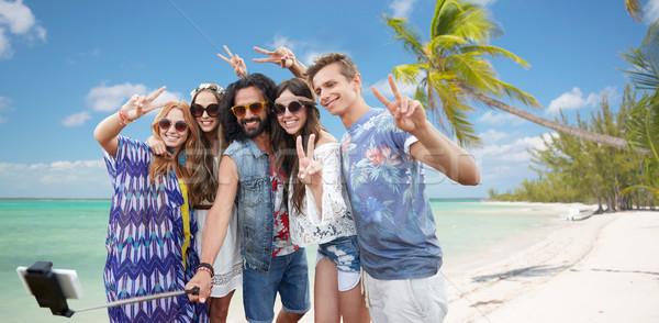 Stock photo: hippie friends with smartphone on selfie stick
