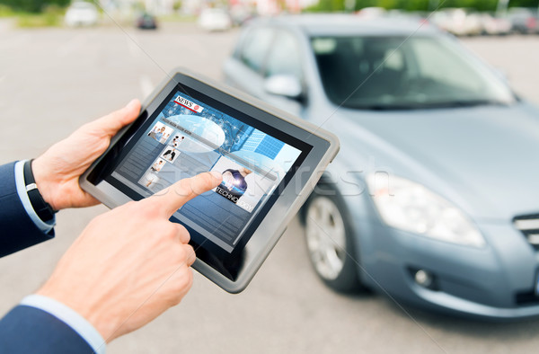 close up of hands with news on tablet pc and car Stock photo © dolgachov
