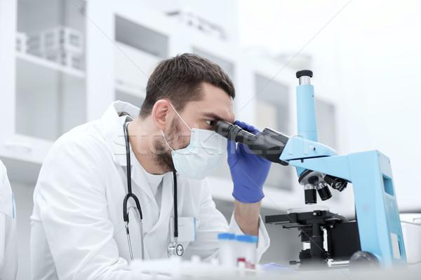 Fiatal tudós néz mikroszkóp labor tudomány Stock fotó © dolgachov