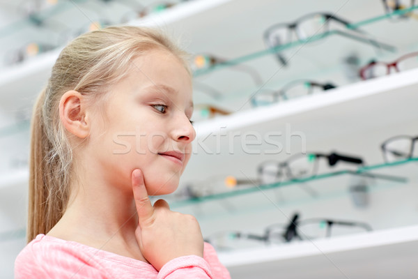 little girl choosing glasses at optics store Stock photo © dolgachov