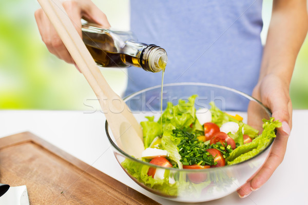 close up of woman cooking vegetable salad at home Stock photo © dolgachov