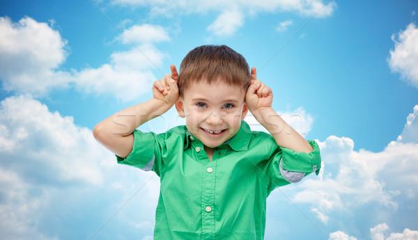 happy little boy having fun and making horns Stock photo © dolgachov