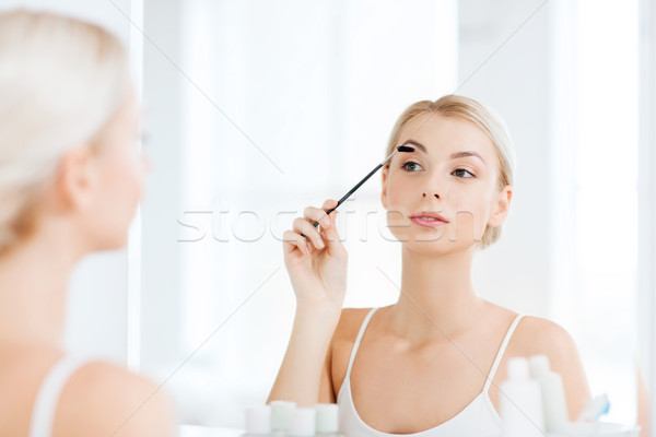 woman brushing eyebrow with brush at bathroom Stock photo © dolgachov
