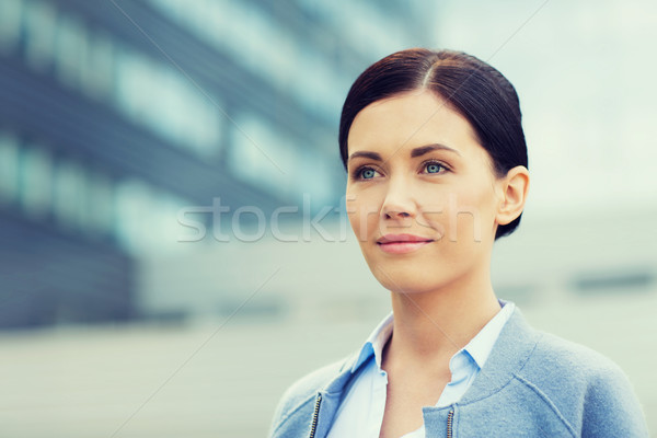 young smiling businesswoman over office building Stock photo © dolgachov