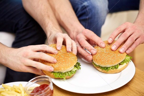 Stock photo: close up of male hands with hamburgers on table