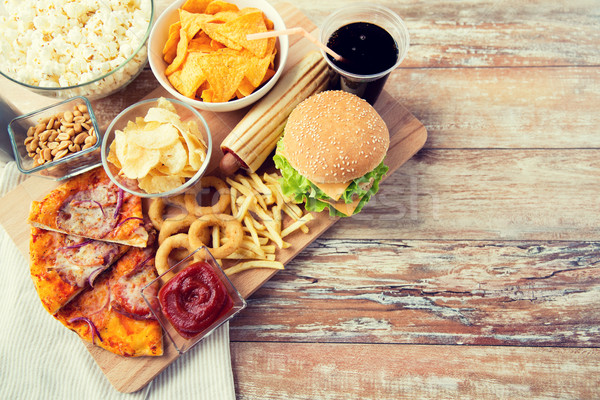 close up of fast food snacks and drink on table Stock photo © dolgachov