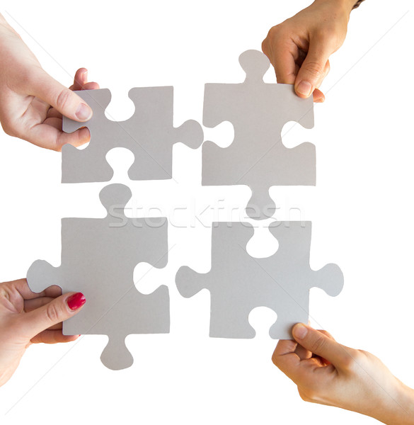 Stock photo: close up of hands connecting puzzle pieces