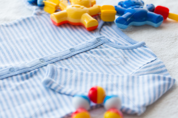 close up of baby bodysuit for newborn and rattle Stock photo © dolgachov