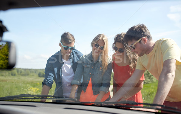 happy friends with map and car searching location Stock photo © dolgachov