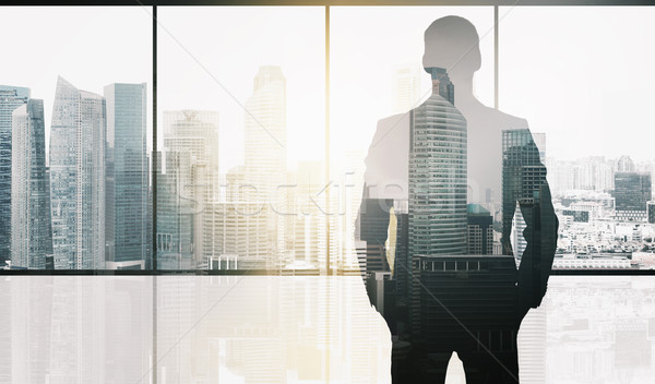 silhouette of business man over office background Stock photo © dolgachov