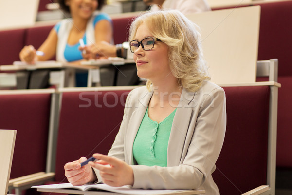 student girl writing to notebook in lecture hall Stock photo © dolgachov