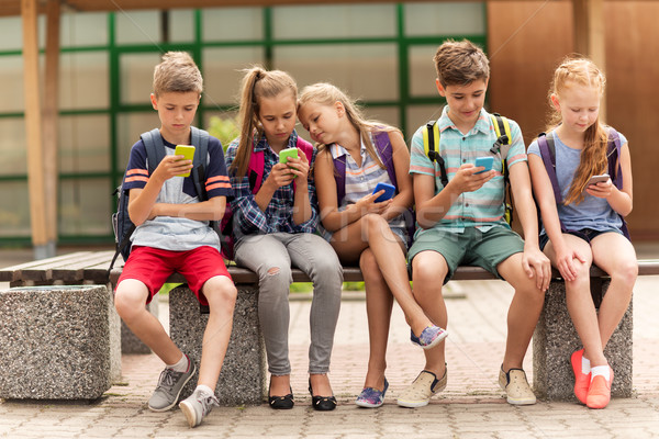 elementary school students with smartphones Stock photo © dolgachov