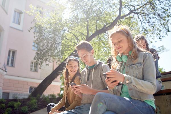 teenage friends with smartphone and headphones Stock photo © dolgachov