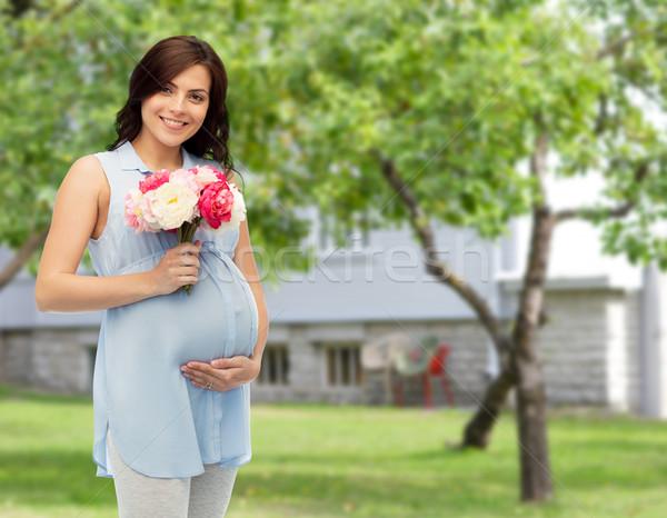 Mutlu hamile kadın çiçekler dokunmak göbek gebelik Stok fotoğraf © dolgachov