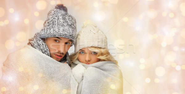 freezing couple in winter clothes wrapped to plaid Stock photo © dolgachov