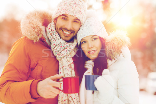 happy couple with tea cups over winter landscape Stock photo © dolgachov